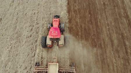 tahıllar : Aerial: top view of an energy-saturated tractor with a trailed seed-tillage unit on support wheels that prepares the soil and sows grain in the spring. Telescopic coverers cover crops
