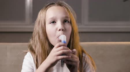 tosse : The procedure of inhalation in the home. The child is undergoing respiratory therapy with a nebulizer. Cute schoolgirl girl cleans her lungs and gets rid of coughing Stock Footage