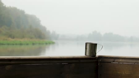 kufel : A metal mug with a hot drink stands on a wooden terrace against the background of a mystical fog over the lake, breakfast in nature, weekend