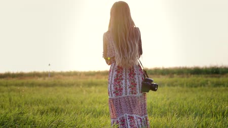 hippie : Rear view of a pretty young hippie woman with a camera on her shoulder walking through an agricultural field at sunset and touching her long hair. Girl in a sundress in nature, slow motion