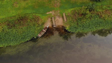abandonné : Fishing, wooden boat moored to the shore, top view. Panorama of the river in which the duckweed floats downstream
