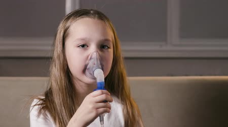 tosse : A small, sad girl treats a respiratory illness with a nebulizer at home. The child inhales through the mask of the inhalation vapor
