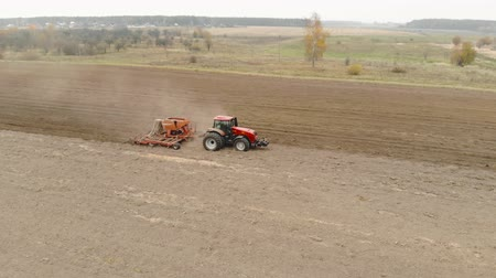 lifeless : Aerial fly-around: farmer on an energy-saturated tractor sows seeds of winter crops on a dusty, lifeless field. Multifunctional seeding unit in action. Agribusiness in agriculture