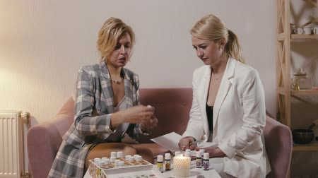 oturum : Two cute adult blondes conduct a session of aromatic psychology. Aromatherapist performs an aroma diagnostics of the client, finds out the psychoemotional state and selects suitable essential oils Stok Video