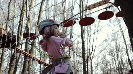 gears : Steadicam shot of a happy little girl in a rope Park against the background of a forest. A child in a helmet and protective equipment passes the track and holds onto the net. Active rest on the nature Stock Footage