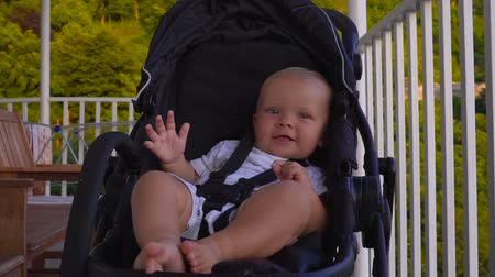 double happiness : Happy baby waving his hand from the stroller