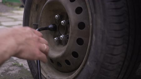 pneus : Close focus on dirty mechanics hands screwing big wheel bolts while changing flat tire on van