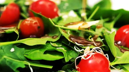 ocet : Pouring reduced balsamic vinegar over green leafs salad with cherry tomatoes Wideo