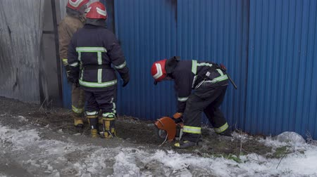 vehicle extrication : Chernivtsi  Ukraine - 03192018: Market with carpets is on fire. Fireman gworking with chainsaw and the axe