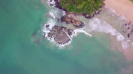 dark bay : Aerial top view waves break on dark rocks near beach. Sea waves on the dangerous stones aerial view drone 4k shot. Sri Lanka