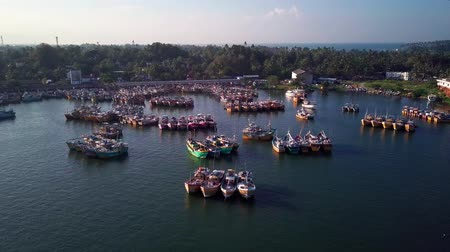 pescador : An aerial, flying view of Bentota, Sri Lanka skyline and a busy fishing harbor with hundreds of fishing boats. Stock Footage