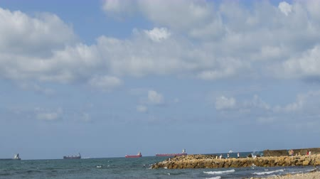 carguero : Timelapse to the sea 4k in Civitavecchia with clouds. Freight ships anchored offshore. The sky with clouds at the sea. The gravel by the sea near the port of Civitavecchia in Italy.