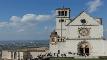 fiel : 25 March 2018, Assisi, Italy. The Cathedral of St. Francis in Assisi with the faithful and tourists outside. 25 March 2018, Assisi, Italy. Timelapse. Timelapse. 4k Stock Footage