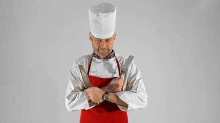 culinária : Handsome adult chef turns, he crosses his arms with knive and spatula, he nods his head on a gray background.