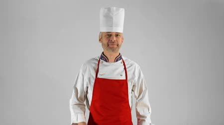 culinária : Handsome adult chef turns, he crosses his arms with knive and nods his head on a gray background.