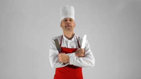 culinária : Handsome adult chef turns, he crosses his arms with knives and nods his head on a gray background. Stock Footage