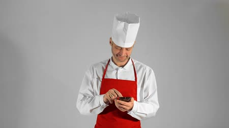 culinária : Handsome adult chef typing on smartphone, then he looking at the camera and smiling on a gray background.