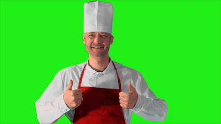 culinária : Handsome adult chef gives the thumbs-up to the camera and smile on a green background. Stock Footage