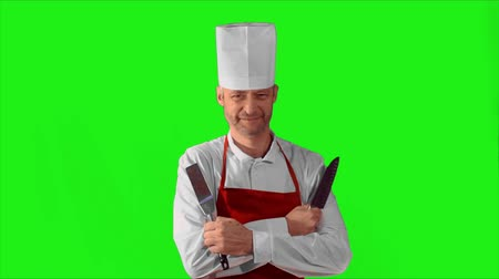 culinária : Handsome adult chef turns, he crosses his arms with knives and nods his head on a green background.