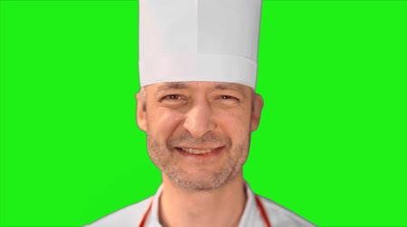 culinária : Handsome chef turns head, smiling at the camera and turns back on a green background. Stock Footage