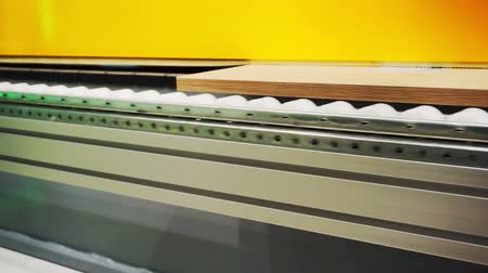 обрабатываются : manufacturing industry.modern woodworking machine with digital control.technological process.conveyor along which the blank moves the furniture panel.fragment of working elements and parts.close-up Стоковые видеозаписи