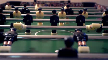 долл : Games, entertainment, hobbies and leisure.foosball.plastic players in the table soccer.game kicker close up.Shallow depth of field