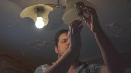 substituição : portrait of a man at homework that replaces light bulbs in an old lamp Stock Footage