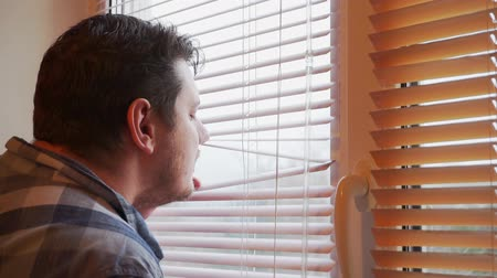 luxaflex : curious man looks out the window through the blinds