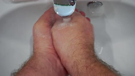 lavatório : hands washing over the sink.male hands rinse with a stream of water.first person view.top view.close-up.