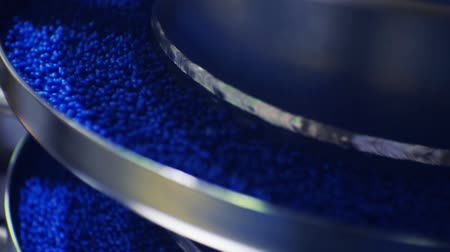 moldagem : vibrating conveyor.blue round granules move up the vibrating screw conveyor