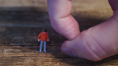 miniatűr : people management.controls a little man on a wooden surface