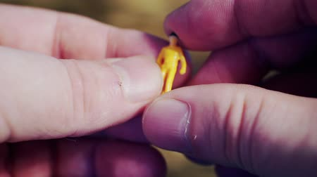 miniatűr : small toy man in the hands of a man.close-up. Stock mozgókép