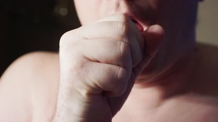 tosse : a middle-aged man coughing and covering his mouth with his fist.Close-up