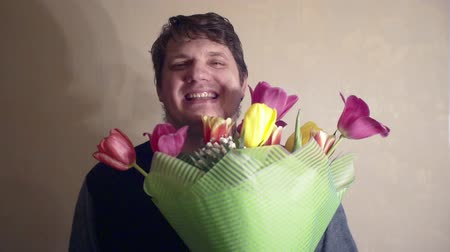 smiling man with a bouquet of spring flowers.