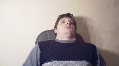 fotel : tired man sleeping in a chair Wideo
