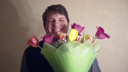 урод : smiling man with a bouquet of spring flowers.