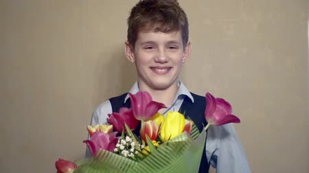 コミカル : smiling boy with a bouquet of spring flowers.