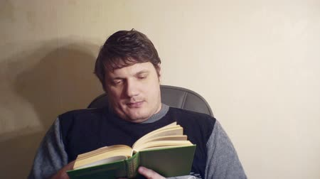 времяпровождение : bored man reads a book while sitting in a chair Стоковые видеозаписи