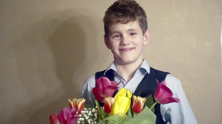 smiling boy with a bouquet of spring flowers.