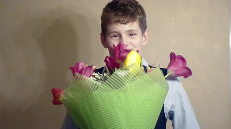 funny smiling boy with a bouquet of flowers