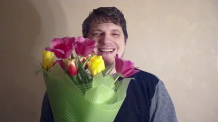 урод : cheerful smiling man with a bouquet of flowers Стоковые видеозаписи