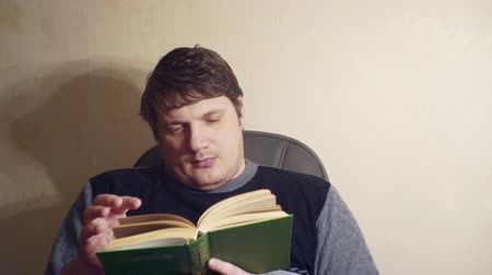 s ennuyer : bored man reads a book while sitting in a chair Vidéos Libres De Droits