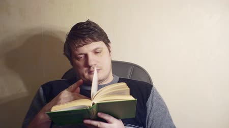 bored man reads a book while sitting in a chair Stock Footage