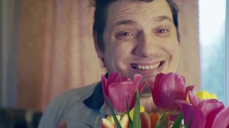урод : cheerful man with a bouquet of flowers.