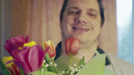Portrait of a funny cheerful man with a bouquet of flowers
