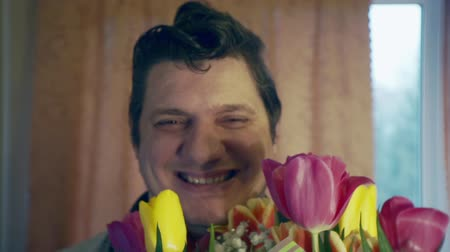 zamilovaný : Portrait of a funny cheerful man with a bouquet of flowers
