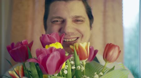 урод : smiling man with a bouquet of spring flowers Стоковые видеозаписи