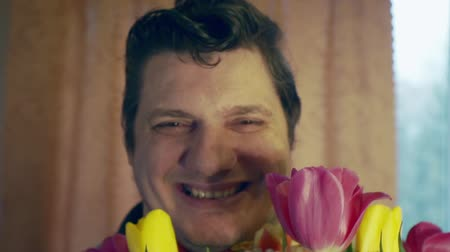 párok : Portrait of a funny cheerful man with a bouquet of flowers