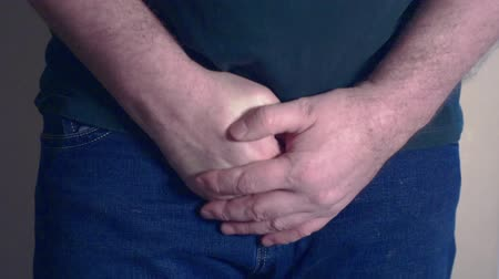 prostata : Man is touching a belt on his jeans