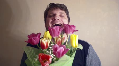 cheerful smiling man with a bouquet of flowers.